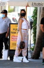 Madison Beer Flashes the peace sign as she waits for her car at the valet after lunch with a mystery man at Il Pastaio in Beverly Hills