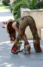 Phoebe Price With her dog and posing with a pair of devil horns in Los Angeles