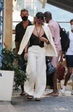 Rita Ora Looks stylish in a white pants suit with a black cami and black sandals while vacationing in Capri