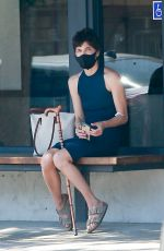Selma Blair In her mask picking up magazines for her reading at home in Los Angeles