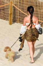 Demi Rose Takes a late afternoon stroll on the beach with her pooch Teddy in Ibiza