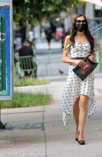 Famke Janssen In a white flowing dress with stars and a clutch featuring a pair of red lips in Soho in New York