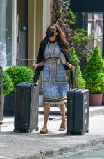 Famke Janssen Wears a protective mask and long patterned dress as she pulls her own luggage in Soho