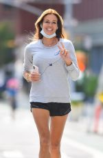 Kelly Bensimon Makes the peace sign while jogging around New York City