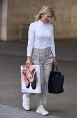 Mollie King Looks sensational in high waist pants and tight wight pullover as she carries beauty products at the Studios in London