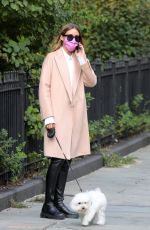 Olivia Palermo Pictured wearing a white short dress under a coat as she takes her dog Mr Butler out for a walk in Manhattan