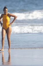 Zoe Saldana and Marco Perego hold hands as they go for a swim in the ocean in Malibu