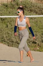Alessandra Ambrosio Gets back to her favorite beach activity to play beach volleyball with her friends before the sun goes down
