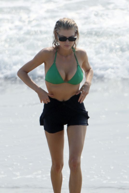 Charlotte McKinney Carries a mini surfboard and wore a green bikini under a black wetsuit in Los Angeles