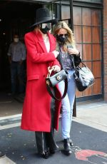 Miley Cyrus Looks chic in a red trench coat paired with black leather pants and a black hat as she heads out in New York