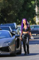 Nikita Dragun Rocks a purple hair do dressed in a pvc outfit for a photoshoot with her Lamborghini in Hollywood