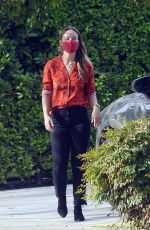 Olivia Wilde Appears to be in high spirits as she waves to a friend in Los Angeles