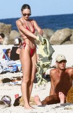 Candice Swanepoel Shows off her perfect figure in a red bikini while out enjoying a beach day in Miami Beach in Florida