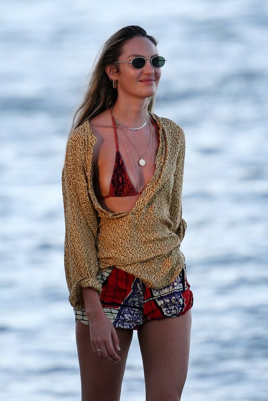 Candice Swanepoel Wears a red snakeskin bikini as she takes a walk on the beach with a friend in Miami