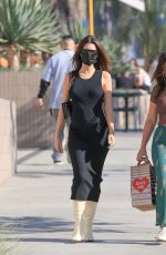 Emily Ratajkowski Shows off her growing baby bump in a skintight black dress
