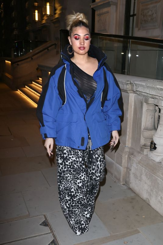 Mabel Looks sensational in a revealing mesh top and flared trousers while out in Soho London