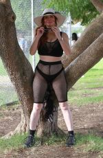 Phoebe Price Seen in black stretching out in the park