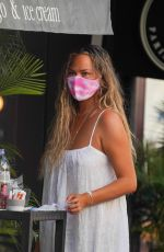 Chrissy Teigen Sits down for a cold drink with friends in Gustavia during her holiday break in St. Barths