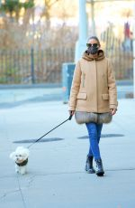 Olivia Palermo Walks her dog Mr. Butler wearing a fur-trimmed Moncler coat, jeans and lace-up boots in New York