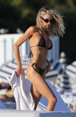 Charlotte Mckinney Shows off her amazing curves in a tiny black bikini on the beach in Miami
