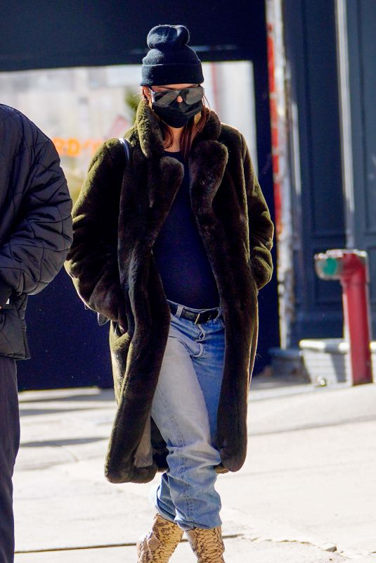 Emily Ratajkowski Wore a black fur coat over a navy blouse paired with distress denim jeans and snakeskin boots in New York