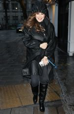 Kelly Brook Dances in the rain looking sensational in knee-high boots and a black coat during a downpour at the Studios in London