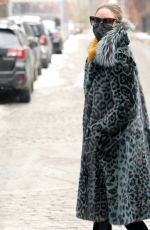 Olivia Palermo Is seen wearing a Cara Mila blue leopard print coat with fuzzy lapels, gold turtleneck and Moncler ski boots in NY