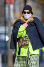 Busy Philipps Wears a neon green cardigan with matching skirt while taking a solo stroll in New York