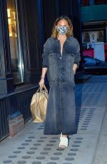 Chrissy Teigen Rocks a unique looking denim dress while out running errands with hubby John Legend in New York