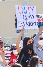 """Lisa Ling Holds a """"Unity Today and Everyday"""" sign as she marches in a """"Stop Asian Hate"""" rally in Koreatown Los Angeles"""