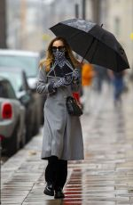 Suki Waterhouse Looks stylish in a double-breasted grey coat on a grey and rainy day in London