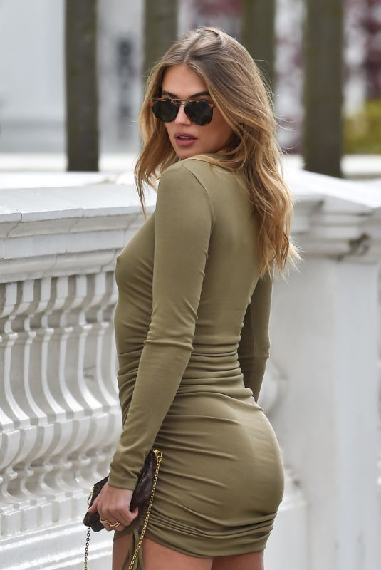 Arabella Chi Is seen braless in a green mini cocktail dress on the streets of London