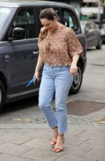 Kelly Brook Wears a floral-patterned blouse and denim jeans at the Heart Radio Studios in London