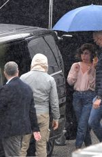 Lady Gaga Is ushered to her car during a rainy day on the set of