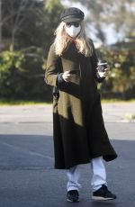 Meg Ryan Grabs a cup of coffee while bundled up in a green pea coat during an early morning coffee run in Santa Barbara