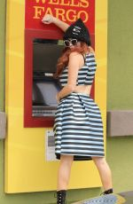 Phoebe Price Pictured smiling and posing at a Wells Fargo ATM displaying her curves