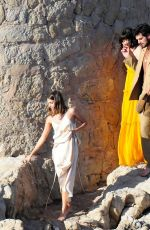 Ana de Armas Wearing a yellow maxi dress on the rocks of a beach during the filming of an advertisement in Mallorca