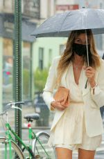 Kelly Bensimon In a little white dress in the rain as she walks back to her real estate office with two colleagues in NY