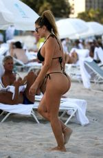 Larsa Pippen In a black bikini as she tests out the water temperature at the beach in Miami