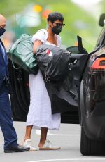 Tamron Hall Wearing a white dress and with her hands full as she laves work in New York