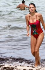 Bethenny Frankel Wears a stylish red one-piece swimsuit and straw hat as she soaks up the sun on Memorial Day weekend with friends in Miami