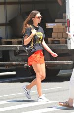 Emily Ratajkowski Dons a gun-printed black tee with orange shorts displaying her legs during a solo outing in NY