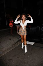 Tinashe Rocks a Burberry skirt paired with a white top and white boots for a night out at Poppy in West Hollywood