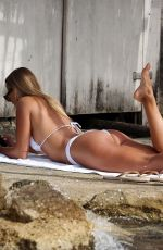 Arabella Chi In a white Prettylittlething bikini while chilling at the beach in Ibiza