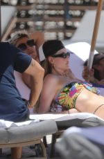 Behati Prinsloo Gets her tanning on at the beach with a few friends in Miami