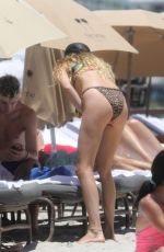 Behati Prinsloo Gets her tanning on at the beach with a few friends in Miami, Florida