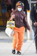 Cardi B In a floral headband and a brown hoodie and orange sweat pants at JFK Airport in New York