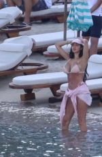 Chloe Khan Puts on a busty display in a tiny pink bikini with a mystery man on holiday in Mykonos