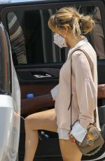 Jennifer Lopez Shows off her flawless legs as she rocked a white button up underneath a chic beige sweater in Santa Monica