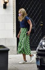 Kelly Ripa Wears a stripe green skirt, blue top, pink mask, and sneakers while out in New York City